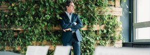 Man in front of a living wall considering CSR and Business Ethics